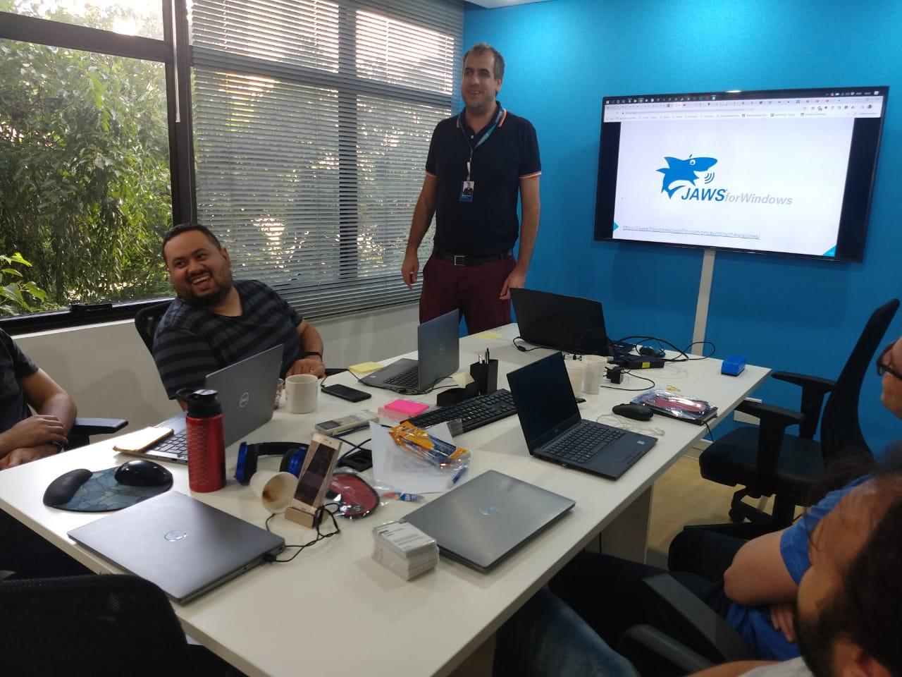 Curso de acessibilidade, foto de uma sala com uma parede azul de fundo, com um quadro branco mostrando a apresentação da aula, no meio uma mesa retangular com quatro alunos sentados ao redor e Daniel (nosso professor) em pé.