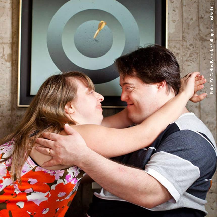 foto de um casal com síndrome de down abraçado e se olhando bastante feliz.