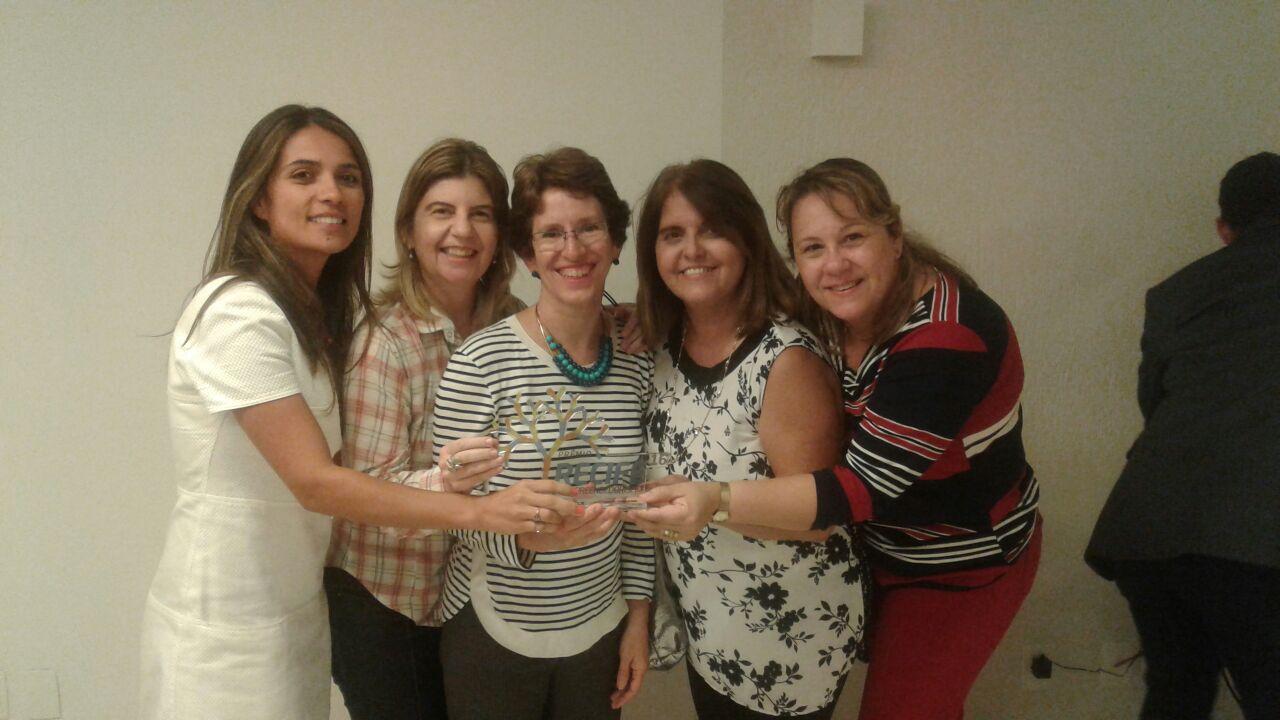 Foto de Virgínia da t-access e da Equipe Sons e Gestos, segurando o troféu Recife Empreendedorismo 2016