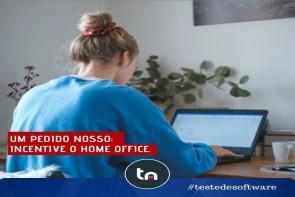 Uma mulher loira de costas, vestindo uma blusa azul, sentada em uma mesa trabalhando de home office.